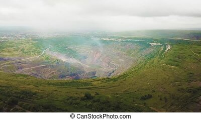 Aerial view industrial of opencast mining quarry with lots of machinery at work - view from above. Extraction of gold, copper