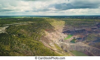 Aerial view industrial of opencast mining quarry with lots of machinery at work - view from above.