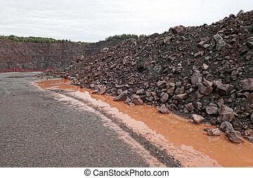 Aerial view into a quarry mine of porphyry rocks.
