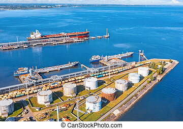 Aerial view large port oil loading terminal with large storage tanks. Railway infrastructure for the delivery of bulk cargo by sea, using pump station in ship tanker for transportation and delivery.