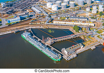 Aerial view large port with railway infrastructure for the delivery of bulk cargo by sea, loading oil using a pump station in ship tanker for transportation and delivery.