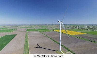 Aerial view looking across wind turbines in motion on a...