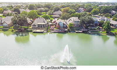 Aerial view luxury waterfront houses with lake fountain in sunny day near Dallas, Texas, USA