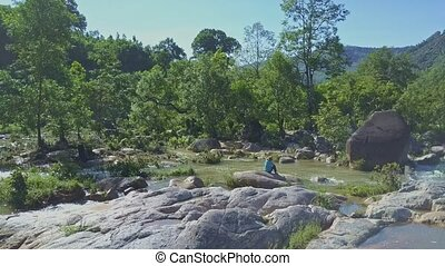 Aerial View Man Sits on Boulder and Fishes at Green Bank -...