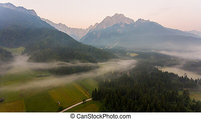 Aerial view mist hovering across a valley.