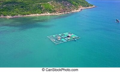 Aerial View Motion down to Floating Lobster Farm by Coast -...