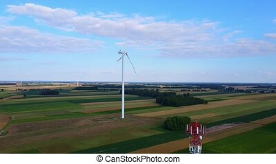 Aerial view of wind energy turbines 5G tower and in summer. Birds eye shot.