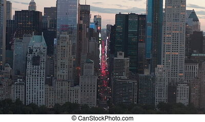 AERIAL: View of 7th Avenue Traffic and Times Square over New York City Central Park at Sunset with City lights