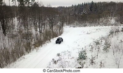 Aerial view of a 6x6 SUV, which rides on a snow-covered road in winter forest. Top view