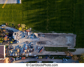 Aerial view of a building construction site at the place of storage of building materials for crushed stone and bricks cement, surrounded by a green lawn with grass at sunset on an autumn sunny day