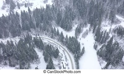 Aerial view of a car driving along a road surrounded by winter forest
