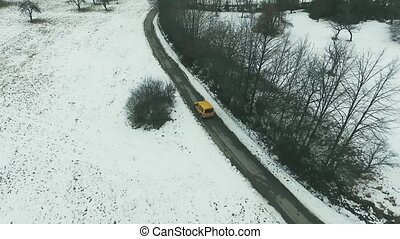Aerial view of a car driving on a road in winter.