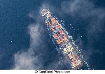 Aerial view of a cargo ship at sea partly covered with...
