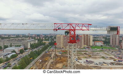 aerial view of a construction crane. It is painted in white and red tones, his white cab. The crane stands at a construction site. Russia, 2016