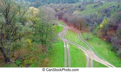 Aerial view of a country road in the mountains among green grass