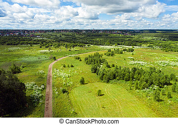 Aerial view of a country road through fields and woods