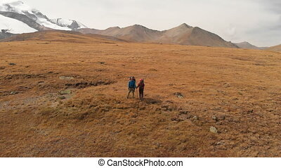 Aerial view of a couple of travelers man and woman with large backpacks in hats and sunglasses stand on alpine plateau surrounded by epic mountains