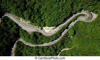 Aerial view of a curved winding road trough the mountains