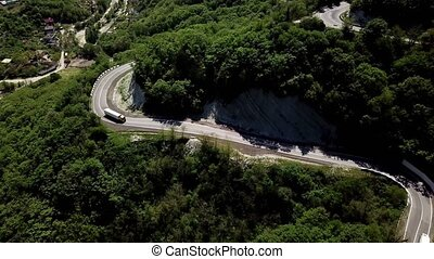 Aerial view of a curved winding road trough the mountains with cars and POV truck.