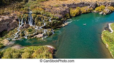 Aerial view of a drift boat floating on the Snake River in Idaho as it passes a waterfall