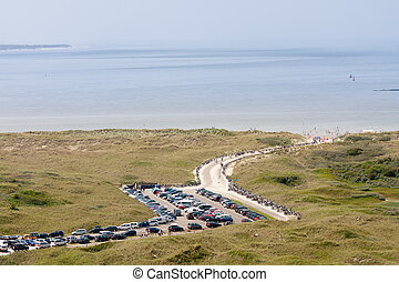 Aerial view of a Dutch beach with dunes and a parking area in front