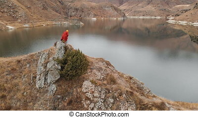 Aerial view of a girl sits down on a rock on the shore of a...