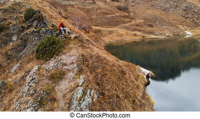 Aerial view of a girl sitting on a rock of a cape on the...