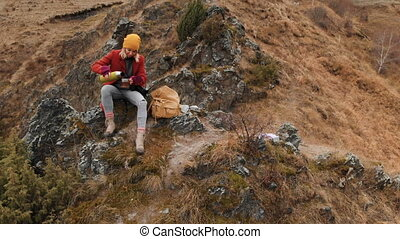 Aerial view of a girl sitting on a rock of a promontory on...