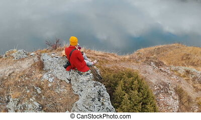 Aerial view of a girl sitting on a rock on a lakeside that...