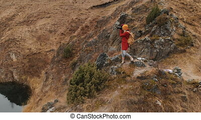 Aerial view of a girl standing on a rock on the shore of a...