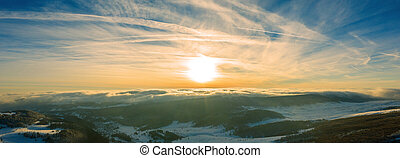 Aerial view of a gold sunset over winter snow. Panorama.