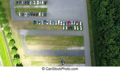 Aerial view of a huge car parking lot panning from the single car to many