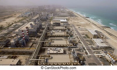Aerial view of a huge power plant on the shore of the sea in Dubai, UAE