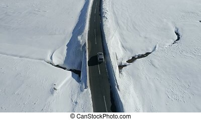 aerial view of a luxury car driving on country road through...