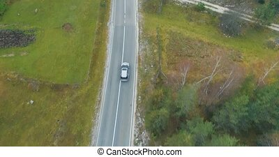 aerial view of a luxury car driving on country road
