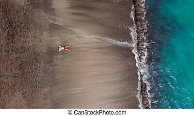 Aerial view of a man in red shorts lies on deserted black...
