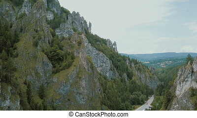 Aerial view of a mountain road in a beautiful deep gorge. Cars move on a mountain road.