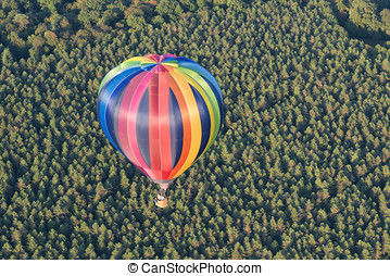 hot air balloon flying over a forest