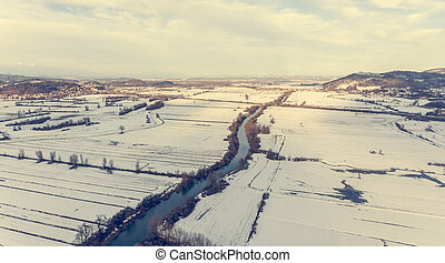 Aerial view of a river flowing through winter countryside.