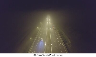 Aerial view of a road traffic in fog at night