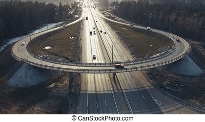 Aerial view of a roundabout, aerial crossing of several roads. Highway panorama in the evening at sunset. Leading innovation concept, finance abstraction, transport logistics and infrastructure. UHD