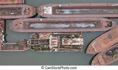Aerial view of a rusting metal shipwreck - A rusting red...