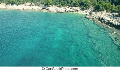 Aerial view of a small crowded rocky beach on the Adriatic sea. Summer vacation time