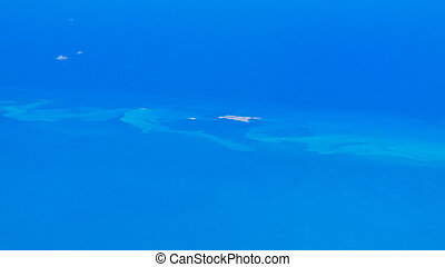 Aerial view of a small island in the Caribbean sea on a sunny day