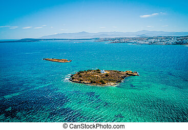 Aerial view of a small island in the sea with a white chapel, Paros