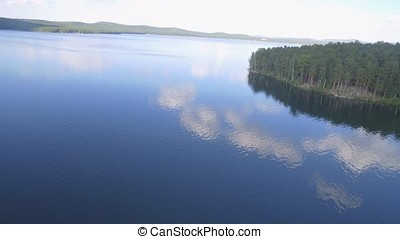 Aerial view of a small lake in the middle of a forest. Beautiful landscape sea, forest and rocks