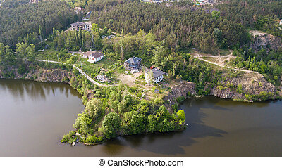 Aerial view of a small river with trees and houses on the shore