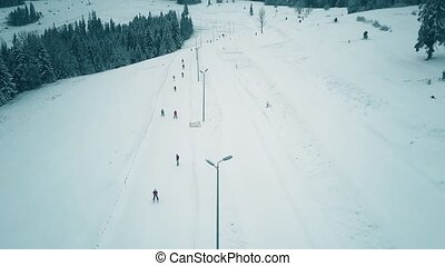 Aerial view of a snow covered alpine skiing slope in winter...