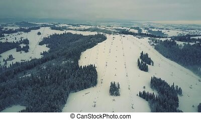 Aerial view of a snow covered alpine skiing slopes in winter. Ski resort in southern Poland, the Tatra mountains