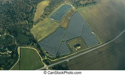 Aerial view of a solar power station and a sheep farm below...